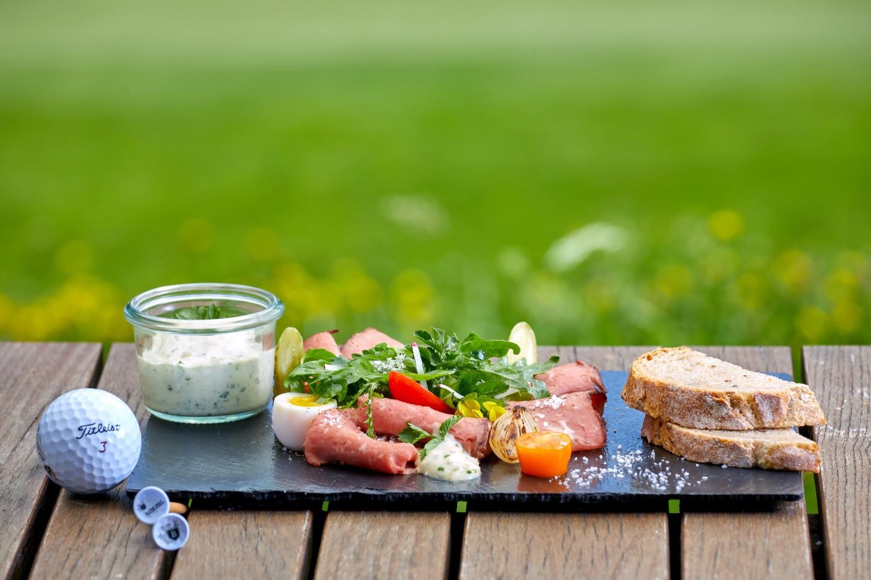 Brotzeit auf einem Schiefergedecktauf im Alpina Golf Restaurant.