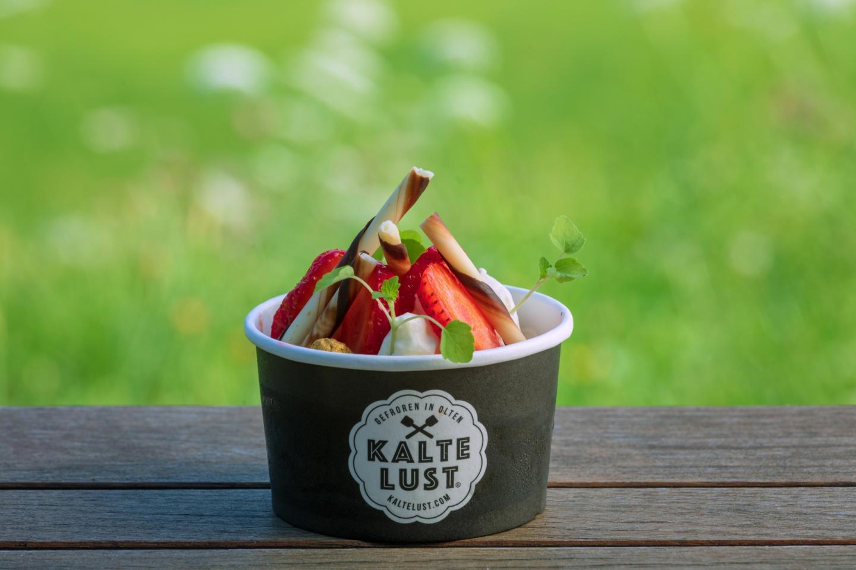 """Traditionelles Eis von """"Kalte Lust"""" in einem Eisbecher mit Erdbeeren verziert."""