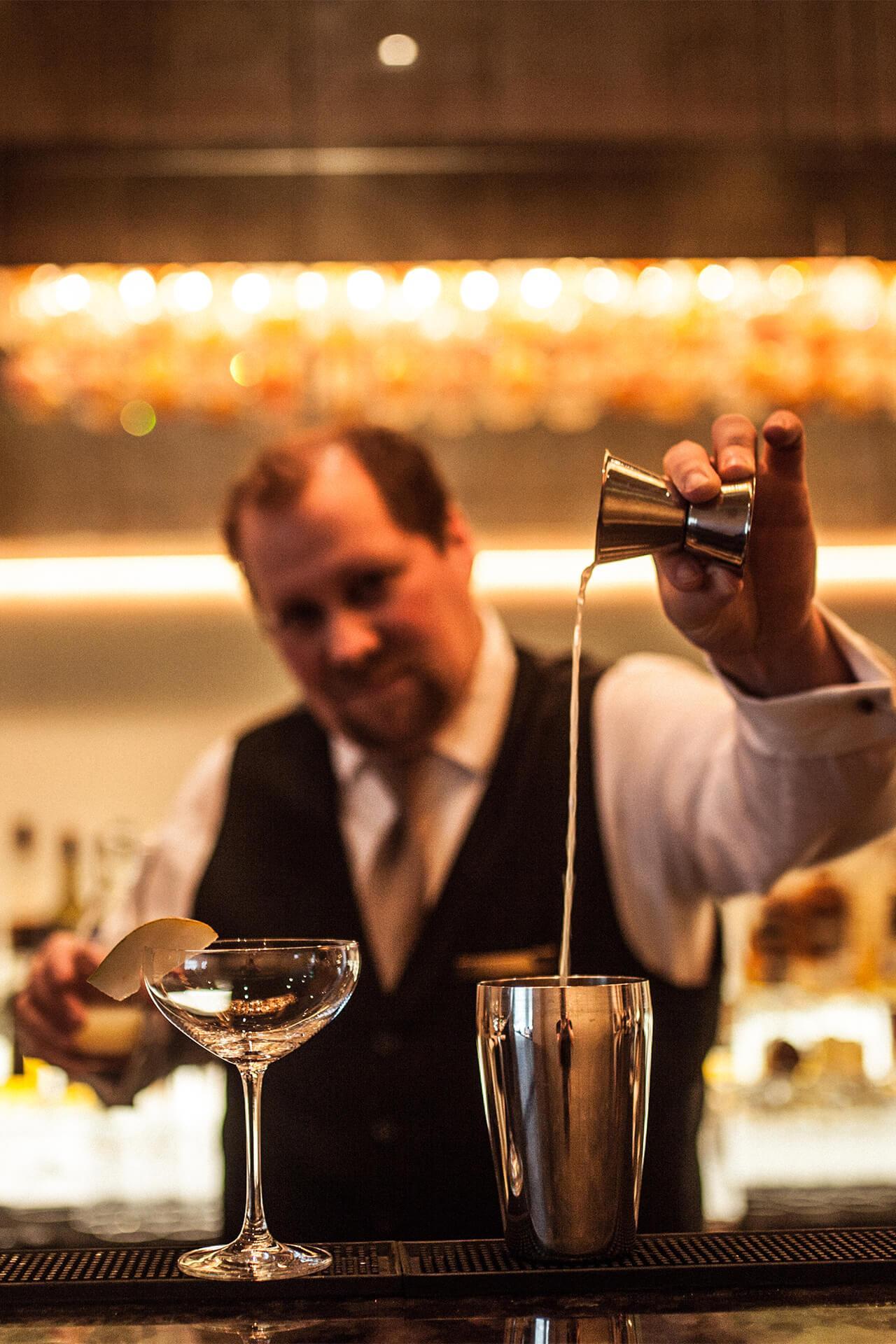 Barkeeper giesst einen Shot in den Cocktailshaker der Bar Bern