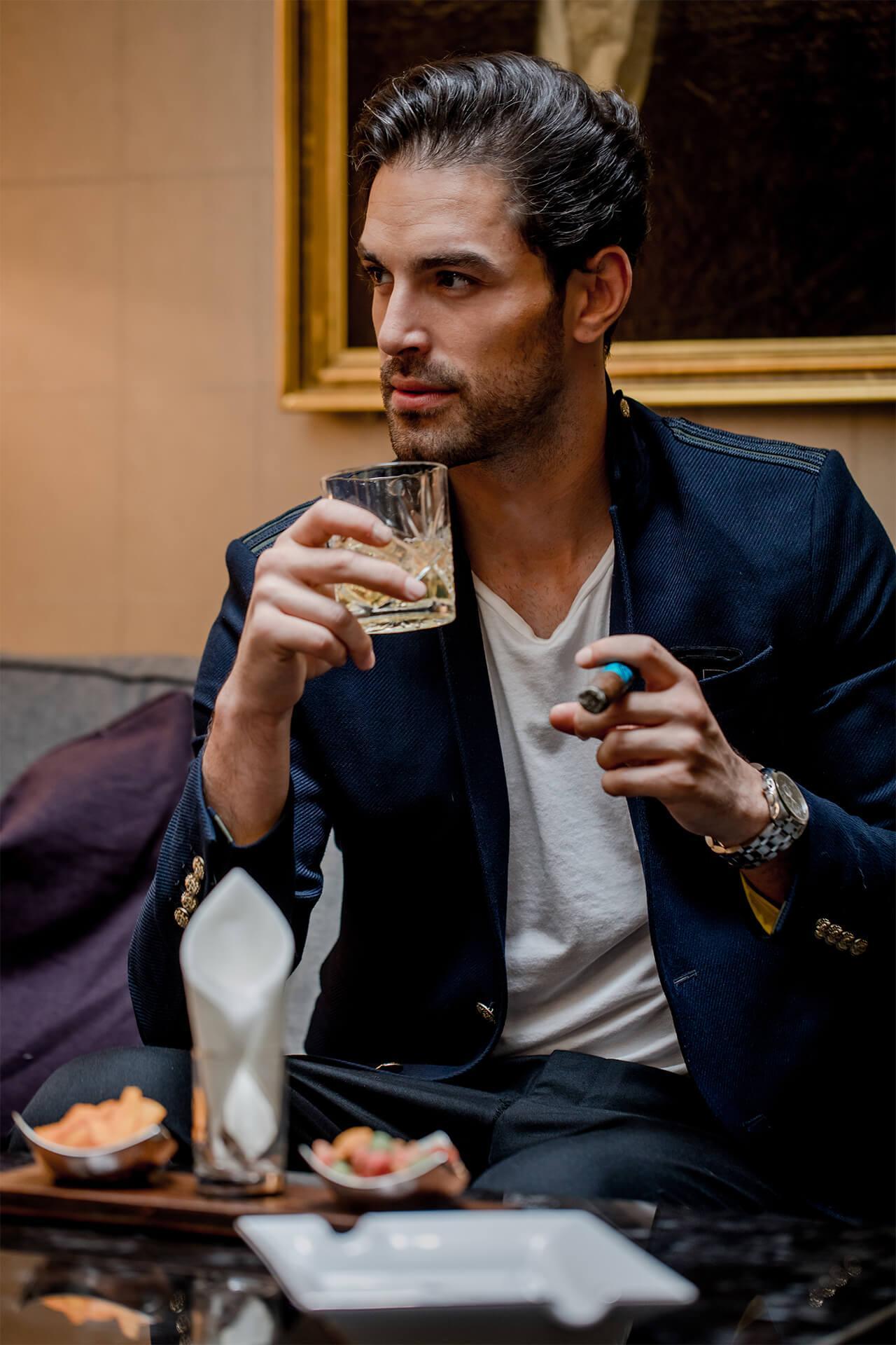 Mann trinkt einen Whiskey und raucht dazu Zigarre in der Zigarrenlounge in Bern