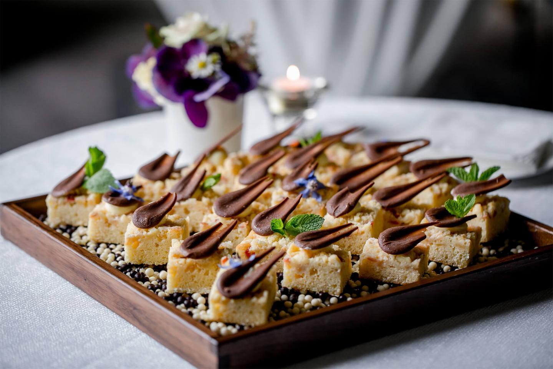 Hübsch angerichtete Kuchenstückchen auf einem Brett mit Dekoration im Restaurants Bern