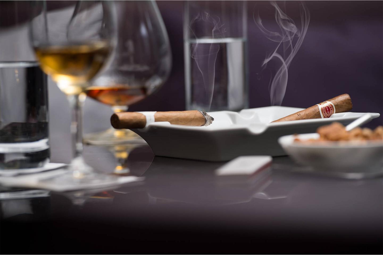 Zwei rauchende Zigarren auf dem Aschenbecher liegend