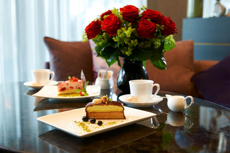 Zwei Tortenstücke auf dem Tisch mit einem rote Rosen-Blumenstrauss in der Bar Bern