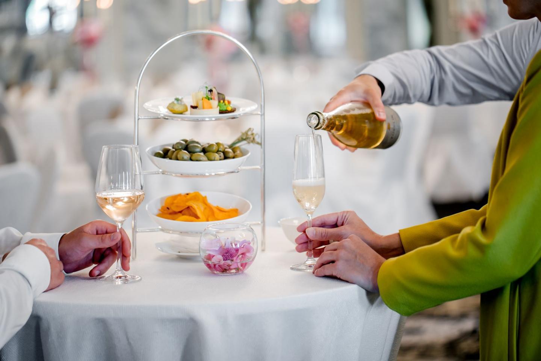 Paar am Stehtisch bekommt Champagner nachgeschenkt
