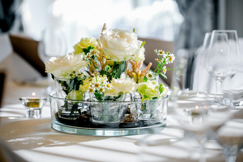 Weisser Blumenschmuck mit Gänseblümchen und weissen Rosen auf dem Tisch des Berner Restaurants