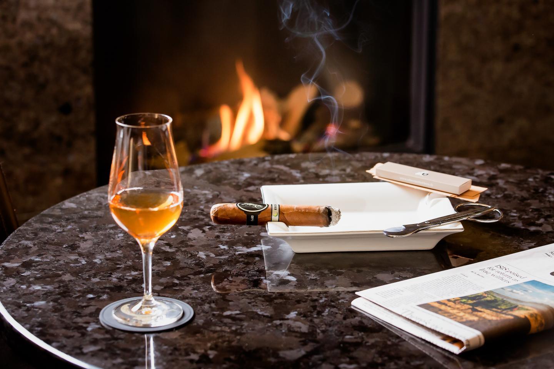 Rauchende Zigarre auf dem Tisch mit einem Glas Whisky in der Whiskylounge des Luxushotel Bern