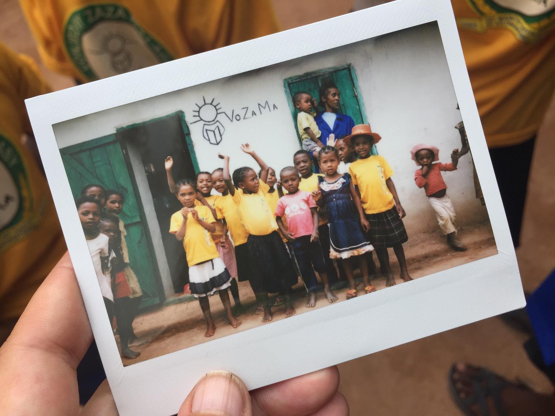 Mann hält ein Diafoto von einem afrikanischen Schulprojekt in der Hand