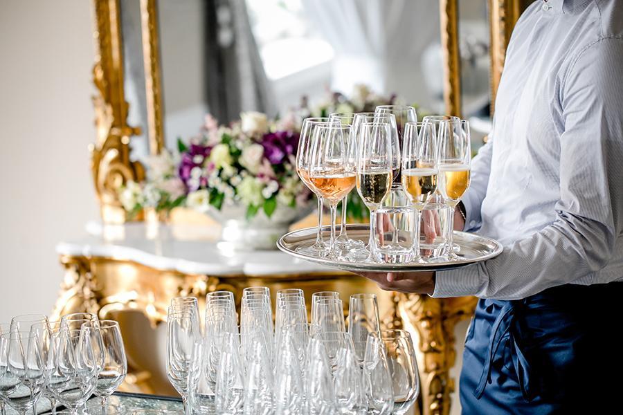 Kellner trägt auf einem Silbertablett mehrere alkoholische Getränke in den Festsaal des Luxushotel Bern